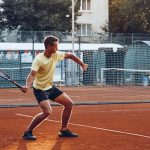 Young handsome man playing tennis on the tennis court
